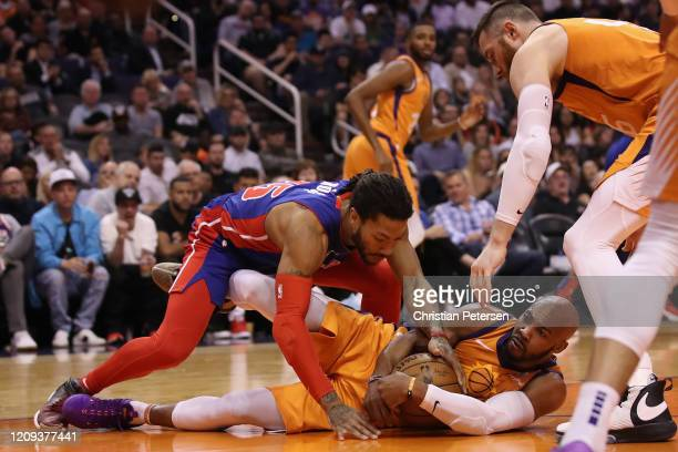 Jevon Carter of the Phoenix Suns and Derrick Rose of the Detroit Pistons fight for a loose ball during the first half of the NBA game at Talking...