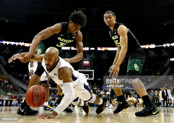 Jevon Carter of the West Virginia Mountaineers dives for a loose ball as Terry Maston of the Baylor Bears defends during the Big 12 Basketball...