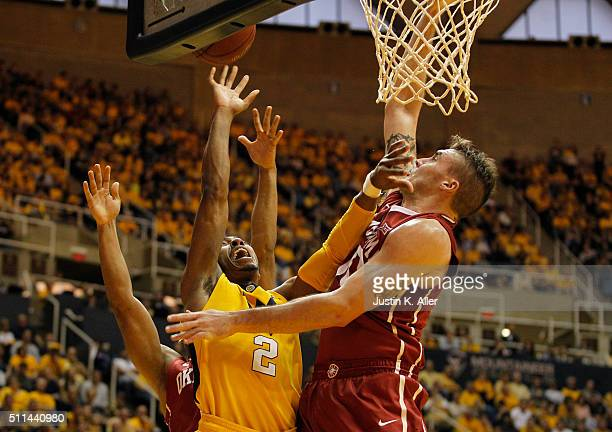 Jevon Carter of the West Virginia Mountaineers drives to the basket against Ryan Spangler of the Oklahoma Sooners during the game at the WVU Coliseum...