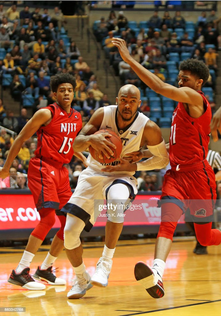 Jevon Carter #2 of the West Virginia Mountaineers handles the ball between Diandre Wilson #15 and Shyquan Gibbs #11 of the N.J.I.T Highlanders at the WVU Coliseum on November 30, 2017 in Morgantown, West Virginia.
