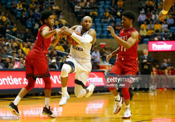 Jevon Carter of the West Virginia Mountaineers handles the ball between Diandre Wilson and Shyquan Gibbs of the NJIT Highlanders at the WVU Coliseum...
