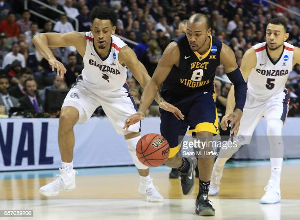 Jevon Carter of the West Virginia Mountaineers is defended by Johnathan Williams and Nigel WilliamsGoss of the Gonzaga Bulldogs during the 2017 NCAA...