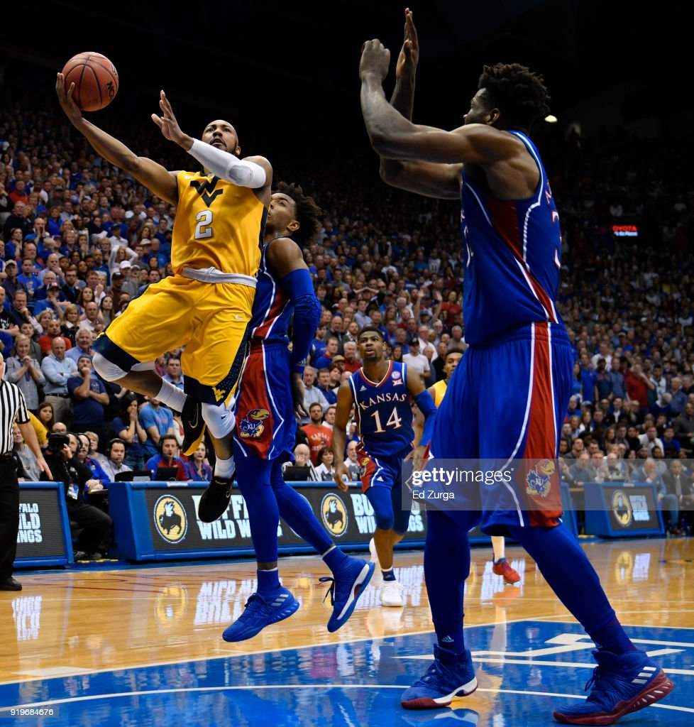 Jevon Carter #2 of the West Virginia Mountaineers lays the ball up against Devonte' Graham #4 and Udoka Azubuike #35 of the Kansas Jayhawks in the second half at Allen Fieldhouse on February 17, 2018 in Lawrence, Kansas.