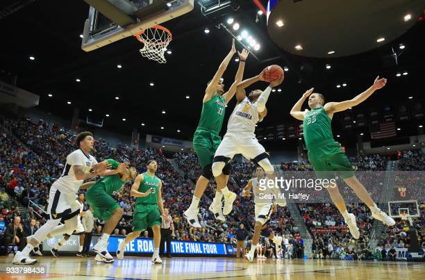Jevon Carter of the West Virginia Mountaineers shoots against Ajdin Penava and Jon Elmore of the Marshall Thundering Herd in the first half during...