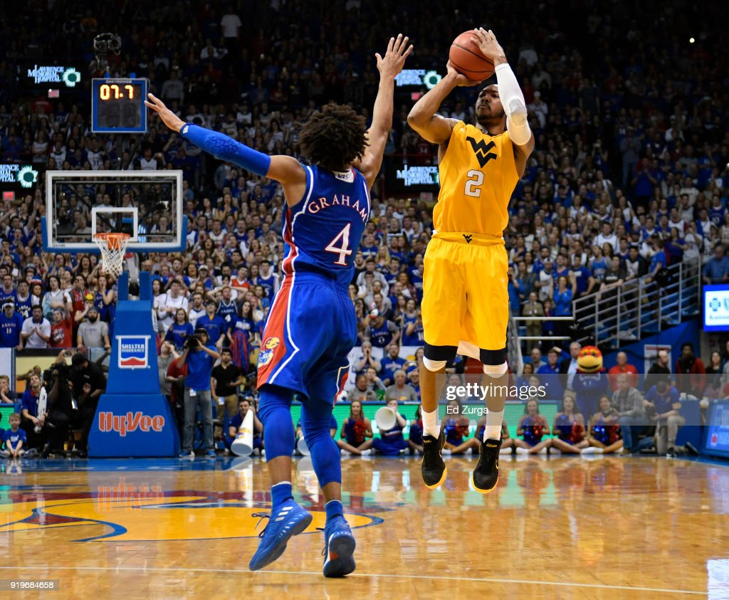 Jevon Carter #2 of the West Virginia Mountaineers shoots against Devonte' Graham #4 of the Kansas Jayhawks in the second half at Allen Fieldhouse on February 17, 2018 in Lawrence, Kansas.