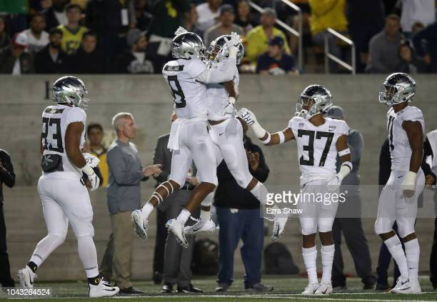 Jevon Holland is congratulated by Thomas Graham Jr #4 of the Oregon Ducks after he intercepted the ball in the endzone against the California Golden...