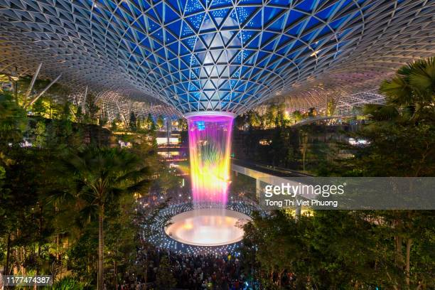 jewel changi airport singapore at night which connecting to terminal 1 arrival and terminal 2,3 through linked bridges - hsbc stock pictures, royalty-free photos & images