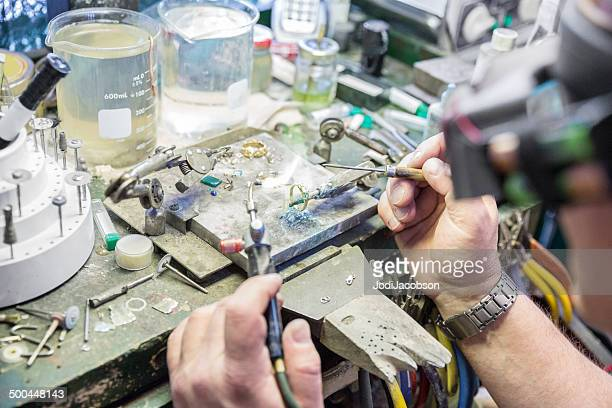 jeweler at his workbench repairing a diamond ring - golden goggles stock pictures, royalty-free photos & images