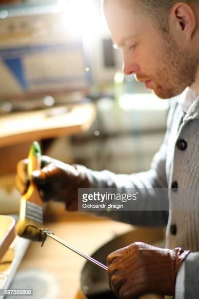Jeweler brushes his tool