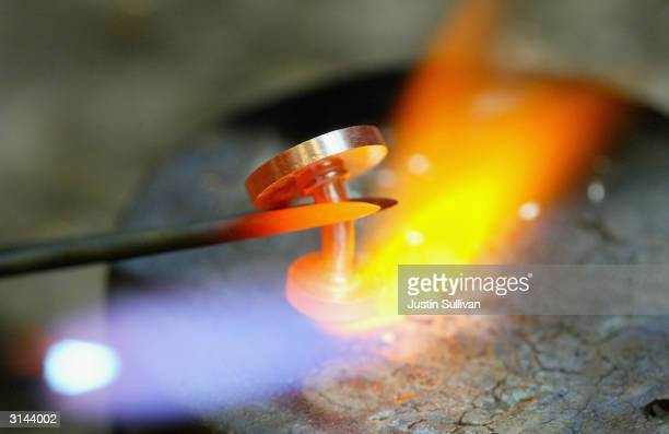 Jeweler Christian Tagle uses a torch to heat up and repair a platinum cufflink at the Union Street Goldsmith March 26 2004 in San Francisco Platinum...