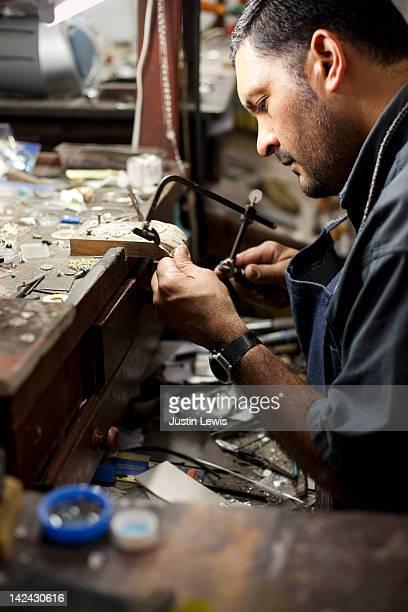 Jeweler making silver jewelery in shop