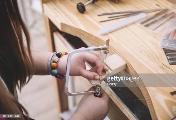 Jeweler using saw to create jewelry
