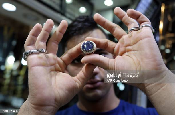 A jeweller checks a ring at a shop in the main market of Iraq's holy city of Najaf on September 13 2017 Strategically located facing the golden gate...