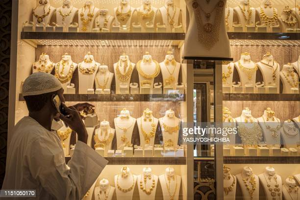A jeweller reaches for a gold ornament in his shop in the Sudanese capital Khartoum's gold market in its downtown district on June 20 2019 Shops...