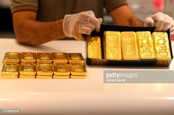 A jeweller wearing a face mask and latex gloves due to the COVID19 coronavirus pandemic showcases bars of gold at a shop at the Dubai Gold Souk in...
