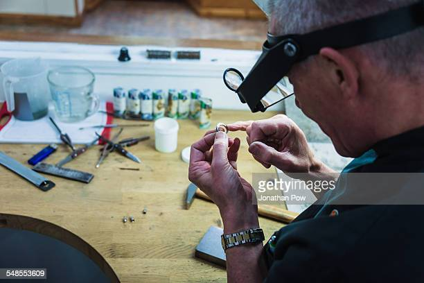Jewellery craftsman touching platinum ring for smoothness