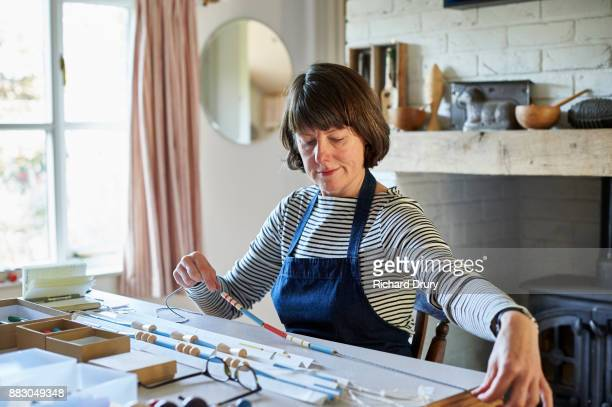 jewellery maker in her workshop - perlenschnur stock-fotos und bilder