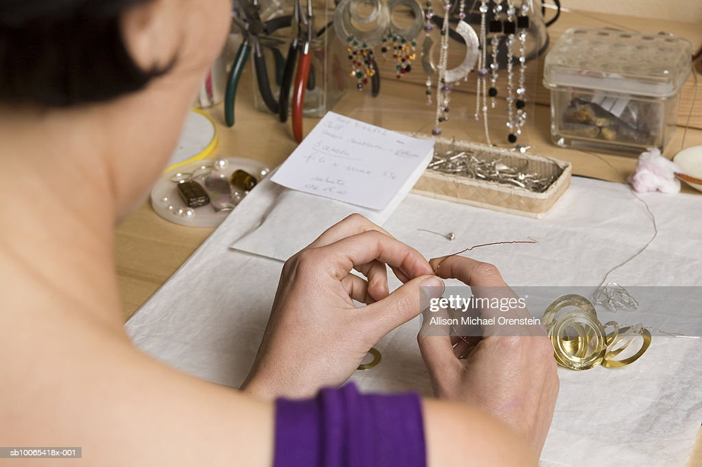 Jewellery maker working on necklace, over the shoulder view : Foto stock