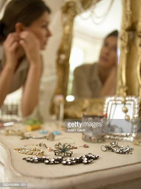Jewellery on dressing table, woman in background