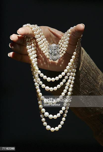 A jewellery specialist from Christie's holds an Art Deco Pearl and Diamond Necklace during a photocall of jewellery and works of art from the...