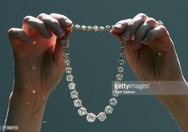 A jewellery specialist from Christie's holds Queen Mary's Diamond Riviere during a photocall of jewellery and works of art from the Collection of Her...