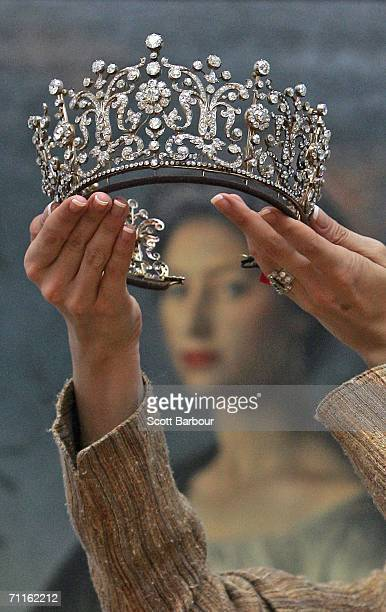Jewellery specialist from Christie's holds the 'Poltimore Tiara' in front of a painting of Princess Margaret during a photocall of jewellery and...