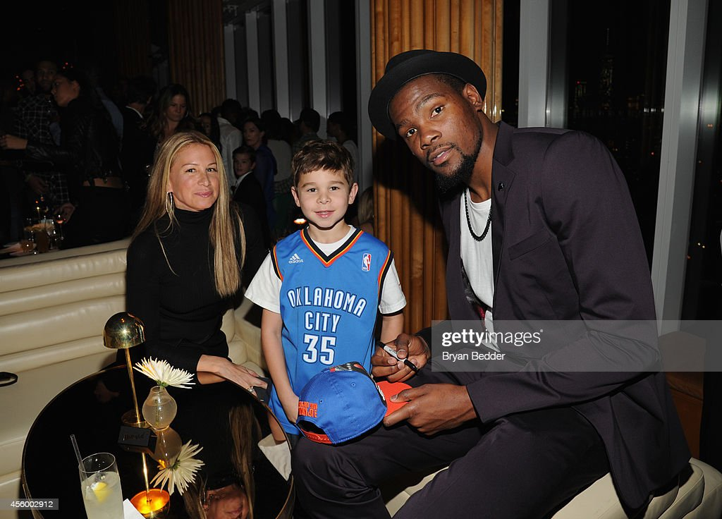 Jewelry designer Jennifer Fisher and son pose for a photo with NBA player Kevin Durant as they attend NBA 2K15 Launch Celebration at The Standard on September 23, 2014 in New York City.