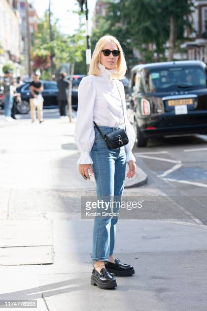 Jewelry designer Sabine Getty wears a white shirt with a ruffle collar and cuffs Mm6 Maison Margiela shoes The Row jeans Celine bag and Cubitts...