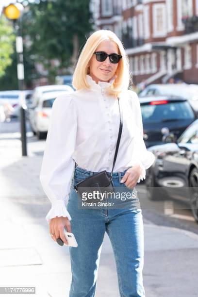 Jewelry designer Sabine Getty wears a white shirt with a ruffled collar and cuffs The Row jeans Celine bag and Cubitts sunglasses during London...