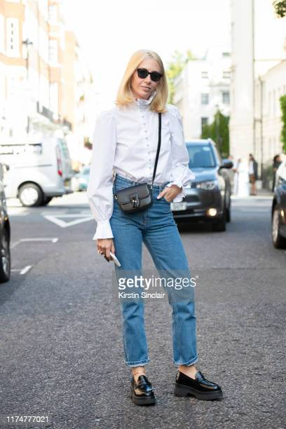 Jewelry designer Sabine Getty wears a white shirt with a ruffled collar and cuffs Mm6 Maison Margiela shoes The Row jeans Celine bag and Cubitts...