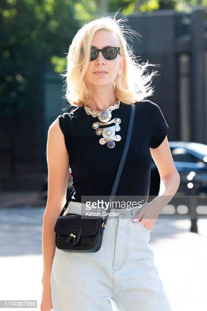 Jewelry designer Sabine Getty wears Cubitts sunglasses a black sleeveless T shirt Pucci necklace Maison Margiela jeans Celine bag during London...