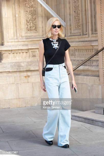 Jewelry designer Sabine Getty wears Cubitts sunglasses a black sleeveless T shirt Pucci necklace Maison Margiela jeans Celine bag and Prada shoes...
