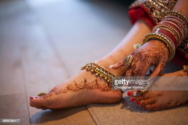 Jewelry is worn over the henna covered hands and feet of an Indian woman.