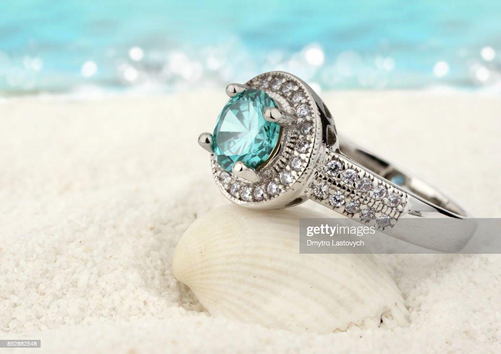 Schmuck Ring mit Aquamarin Edelstein auf Sand Strand Hintergrund : Stock-Foto