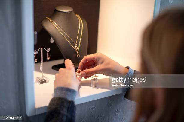 a jewelry store owner arranging her display case. - store opening stock pictures, royalty-free photos & images
