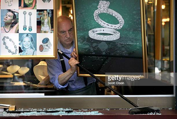 Jewelry store owner cleans broken glass from a window shattered by demonstrators protesting the G8/G20 summits on June 26, 2010 in Toronto, Ontario...