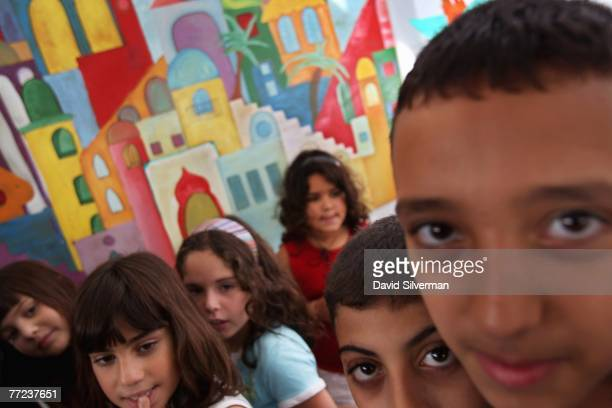 Jewish and Arab children play in front of a mural at the Hand in Hand Center for JewishArab Education October 9 2007 in Jerusalem Israel The...