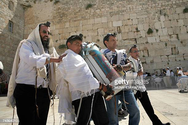 Jewish boy carries the Torah or holy script at the Western Wall Judaism's most holy site as boys participate in their Bar Mitzvah traditionally to be...