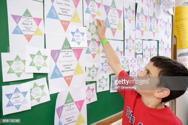 A Jewish boy pledging a star of David on a bulletin board at the Carnival for a Cure