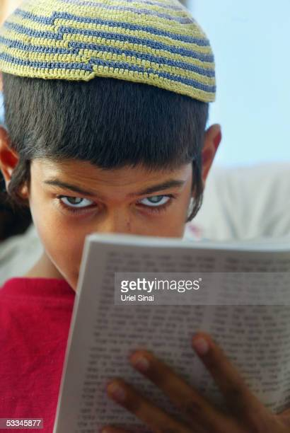 Jewish boy prays during a mass prayer aimed against the Israeli disengagement plan August 9 2005 at the settlement of Neve Dekalim in Gush Katif...