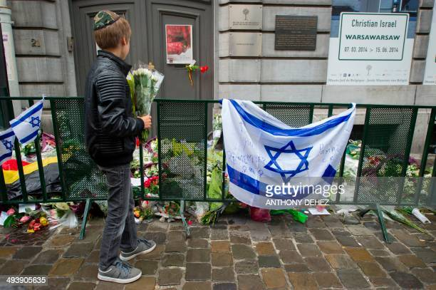 Jewish boy stands with flowers in front of an Israeli flag and flowers laid in front of the Jewish Museum in Brussels on May 26 two days after the...