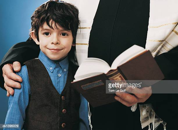 Jewish Boy Stands With Man Beside him Holding an Open Copy of a Holy Book