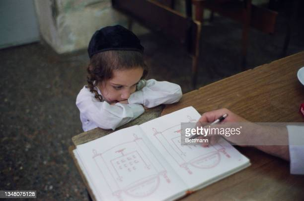 Jewish boy wearing a black yarmulke, his hair styled with payot, or sidelocks, his elbows resting on a desk as possibly a teacher points to...