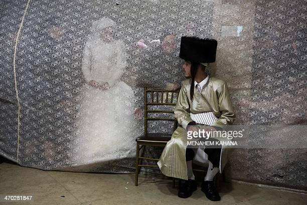 Jewish bride Rivka Hannah looks at her groom Aharon Krois from behind a curtain during the Mitzvah Tans dance ritual following their wedding in an...