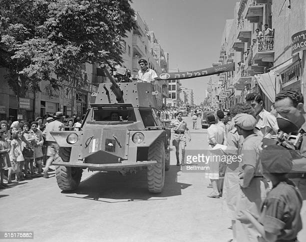 A Jewish car passes an impressed crowd on Ben Yehuda Street during display of military might on eve of end of original UN truce Fighting has stopped...