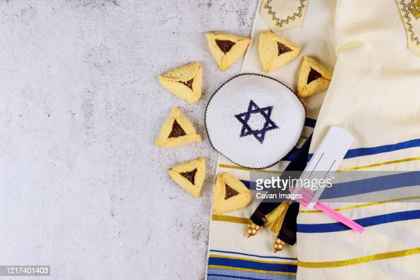 jewish carnival purim celebration on hamantaschen cookies, noisemaker and mask with parchment - jewish prayer shawl stock pictures, royalty-free photos & images