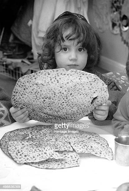 Jewish child holding Passover matzot Edgware London 29 March 1991 Chaim Yosef Abelasis holds a piece of the unleavened bread which is traditionally...