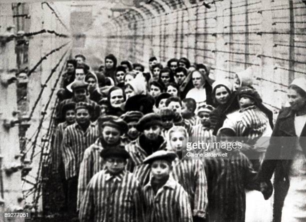 Jewish children, survivors of Auschwitz, with a nurse behind a barbed wire fence, Poland, February 1945. Photo taken by a Russian photographer during...