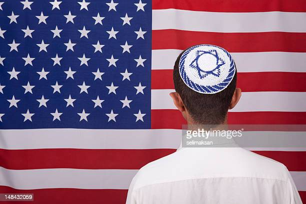 jewish citizen wearing yarmulke in front of american flag - judaism stock pictures, royalty-free photos & images