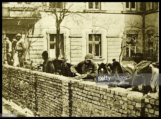 Jewish civilians in Krakow, Poland, are forced to build a brick wall, forming a ghetto for the Jewish community. Dated 1939.
